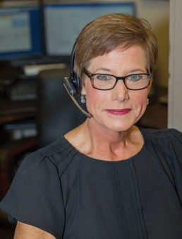 Woman wearing telephone headset.