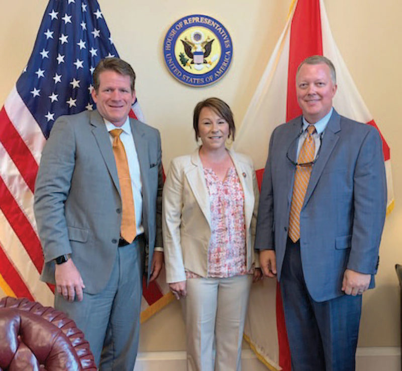 Sean Strickler, Brad Kimbro, and Martha Roby standing in front of the American flag.
