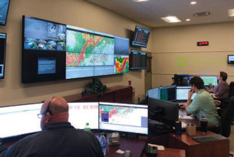 Employees looking at many screens showing the storm weather.