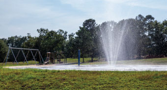Water shooting out of the ground at a playground.