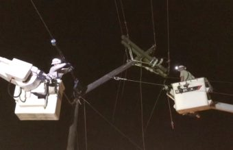linemen in bucket truck working on power poles at night