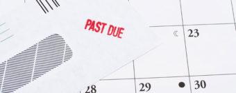 Past due envelope sitting on a calendar.