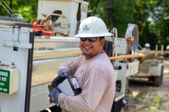 Lineman smiling while working outside near truck.