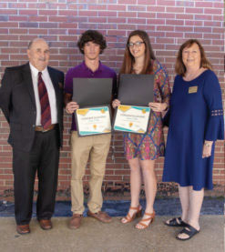 Parents standing next to a girl and boy holding scholarship awards.