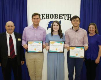 Several students holding scholarship awards.