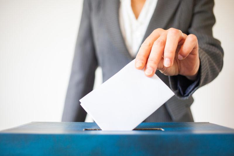 woman putting ballot in slot