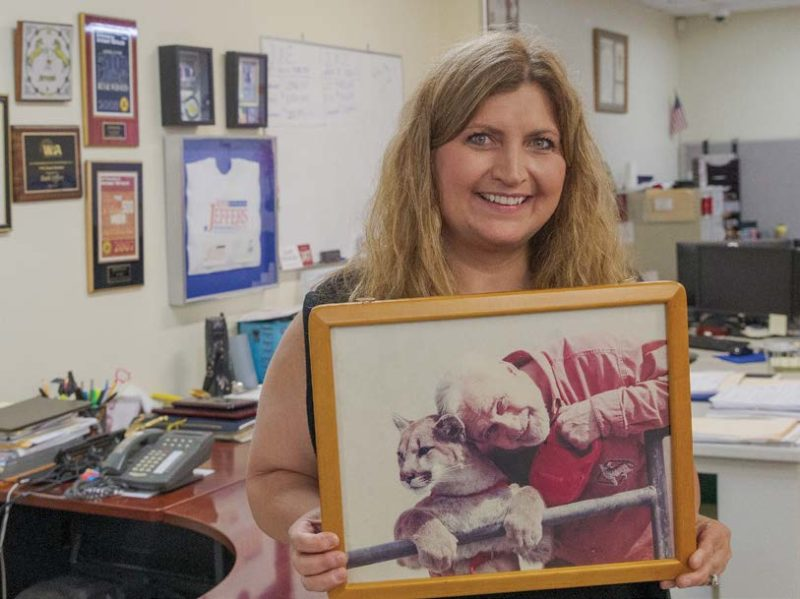 CEO Ruth Jeffers holds a photo of her late father, Dr. Keith Jeffers, and his pet mountain lion, K.C., which stands for Kitty Cat.