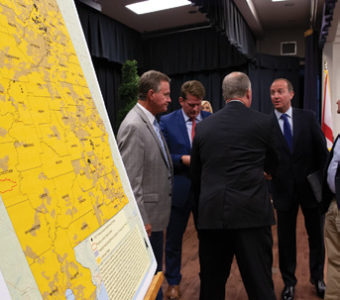 Several men talking next to a large map.