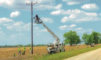 Linemen working on power pole outside.
