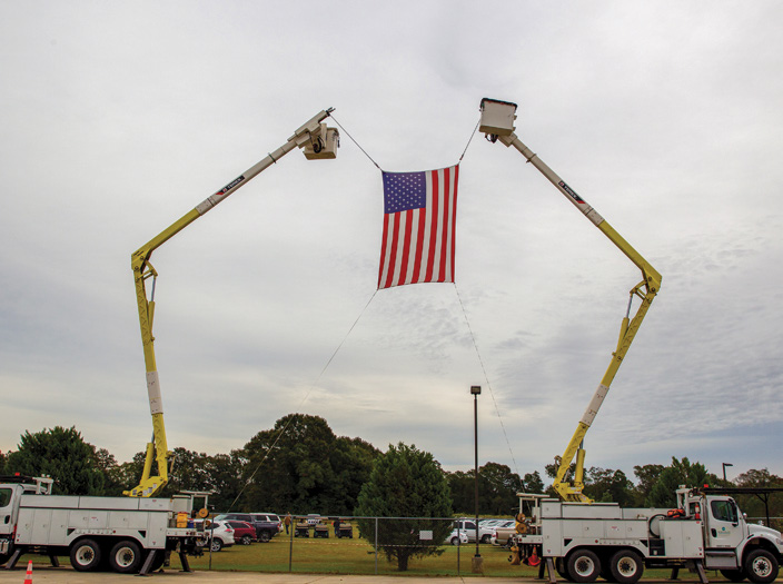 Bucket trucks holding up the American flag in the air.