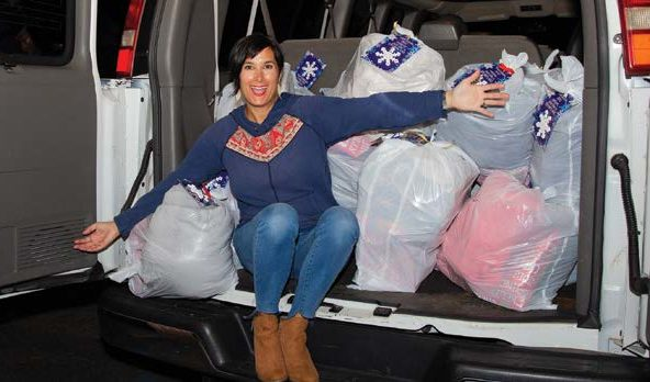 Brandee Lukas in the back of a van filled with bags of presents.