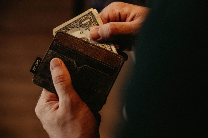 Hand putting money in wallet