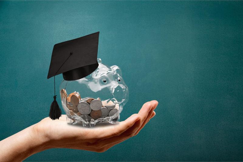 hand holding piggy bank wearing graduation cap